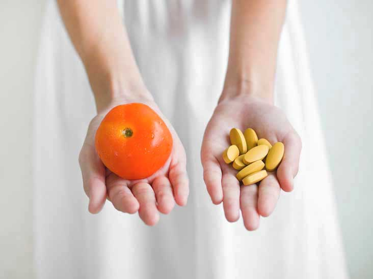 hands-holding-tomato-and-pills